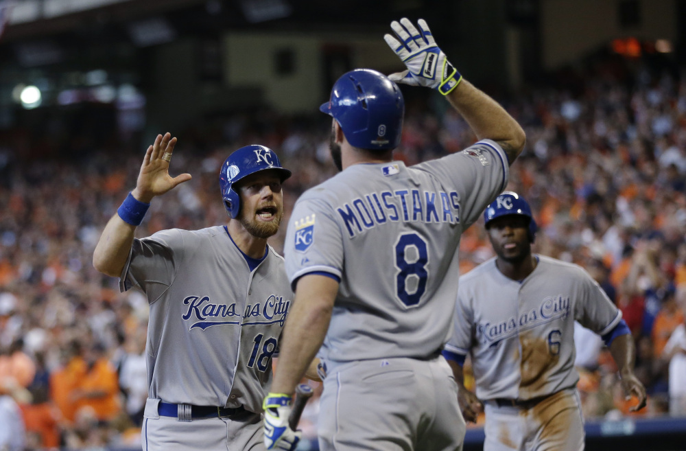 Kansas City's Ben Zobrist (18) celebrates with teammate Mike Moustakas after he and Lorenzo Cain (6) scored during a five-run rally in the eighth inning of Monday's American League Division Series game in Houston.