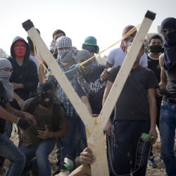 Palestinians use a large handmade slingshot to hurl a stone during clashes with Israeli troops near Ramallah in the West Bank on Monday. Recent weeks have seen a series of stabbing attacks in Israel and the West Bank.