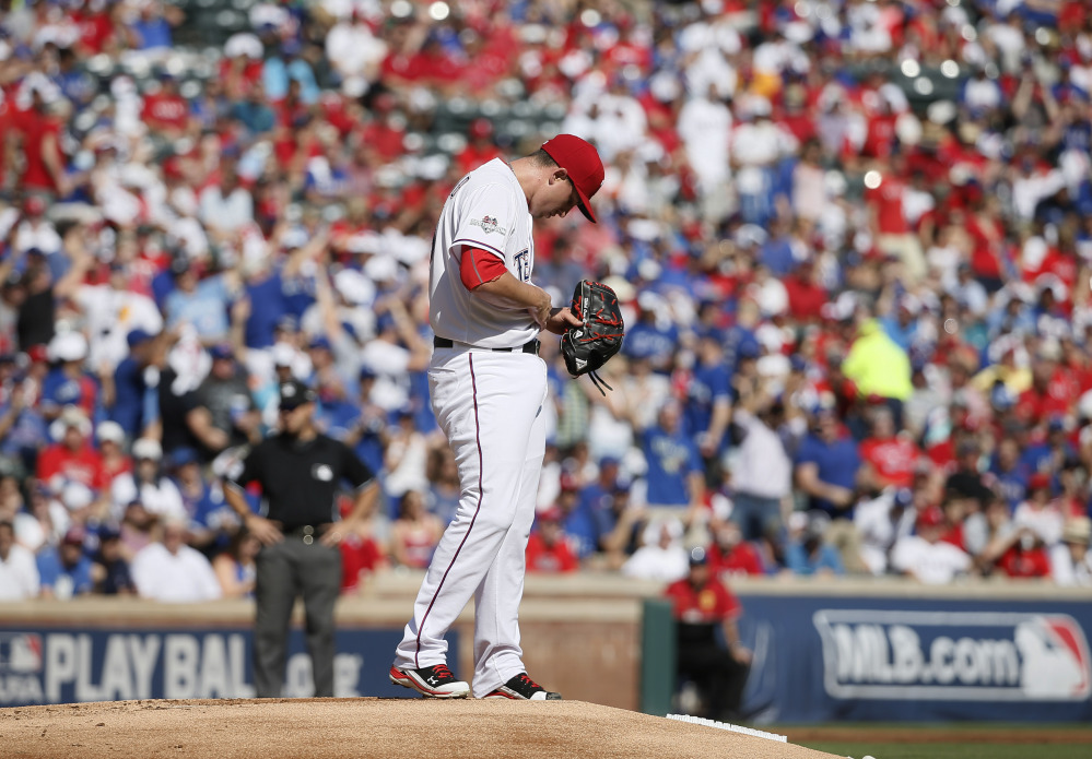 Rangers starting pitcher Derek Holland pauses after Josh Donaldson's home run. Holland lasted just two innings, giving up six runs on five hits.