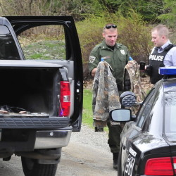 Game warden Dave Ross, left, and Winslow Police Detective Ryan McGowen look over turkey hunting gear belonging to Janice and Reginald Jacques on May 5 after Janice Jacques accidentally shot her husband while turkey hunting. Janice Jacques pleaded guilty to a misdemeanor charge last month.