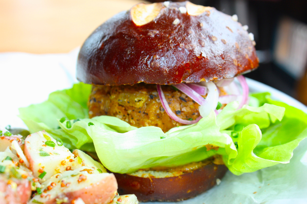 The veggie burger at LFK in Portland is made from red lentils, leeks, roasted cashews, mushrooms and panko breadcrumbs. It is served on a pretzel bun from Rosemont Bakery with a side of vegan potato salad.