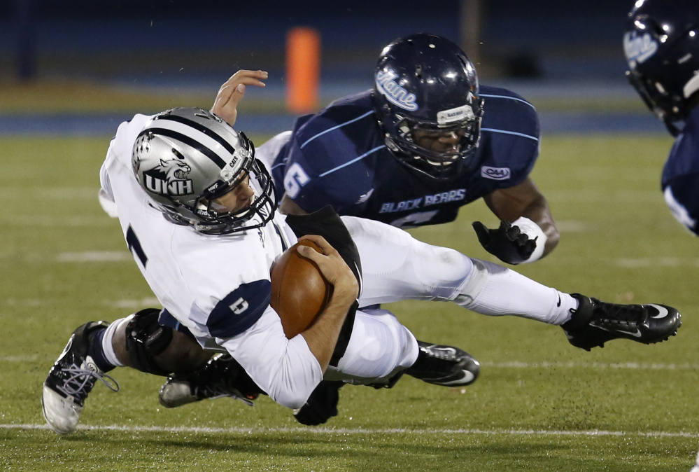 Maine Black Bears linebacker Christophe Mulumba Tshimanga tackles New Hampshire Wildcats quarterback Sean Goldrich in a game at Alfond Stadium in Orono last year. (AP Photo/Robert F. Bukaty)