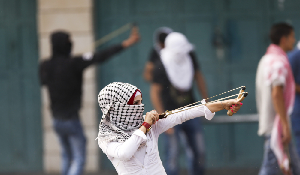 A Palestinian woman uses a slingshot during clashes with Israeli troops in the West Bank city of Bethlehem on Tuesday.