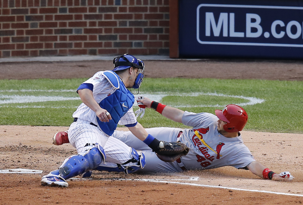 Cubs catcher Miguel Montero tags out the Cardinals' Tony Cruz on a play in the sixth inning. The Cubs got out of the inning in a 4-4 tie and took the lead in the bottom half of the inning.