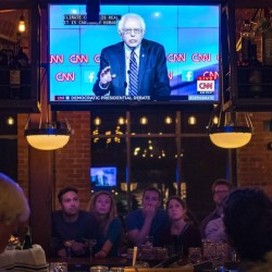 People watch the Democratic presidential debate from Las Vegas at a restaurant in Winooski, Vt. The Vermont Democratic Party sponsored the viewing party. Vermont Sen. Bernie Sanders, on the television screen, was challenged often by Hillary Clinton.