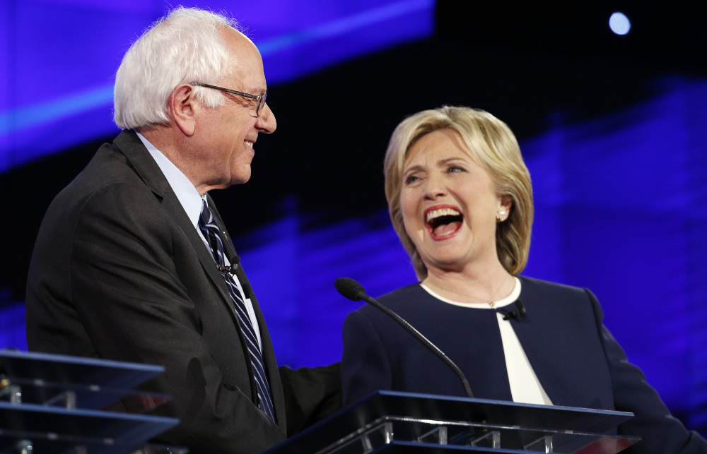 Sen. Bernie Sanders of Vermont and former Secretary of State Hillary Clinton share a laugh at the CNN Democratic presidential debate Tuesday evening in Las Vegas.