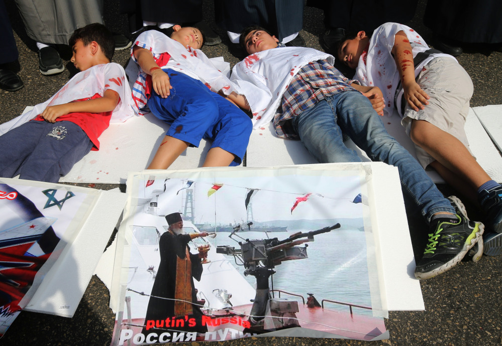 Lebanese boys depict Syrian boys who were killed by Russian airstrikes, during a sit-in in front the Russian embassy in Beirut, Lebanon, Wednesday.