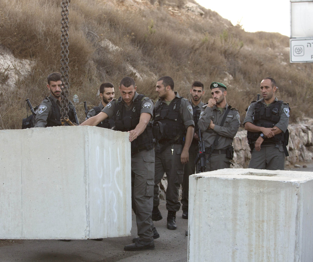 Israeli border officers help place barriers at the entrance of an east Jerusalem neighborhood Wednesday. Despite the escalated security, two assaults were reported – the stabbing of a 70-year-old woman near a bus station and the attempted knifing of police officers outside the Old City. The Associated Press