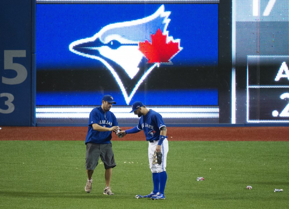 Kevin Pillar of the Blue Jays hands beer cans to a member of the grounds crew during an outburst by Toronto fans in the seventh inning after the umpires awarded Texas a disputed run.