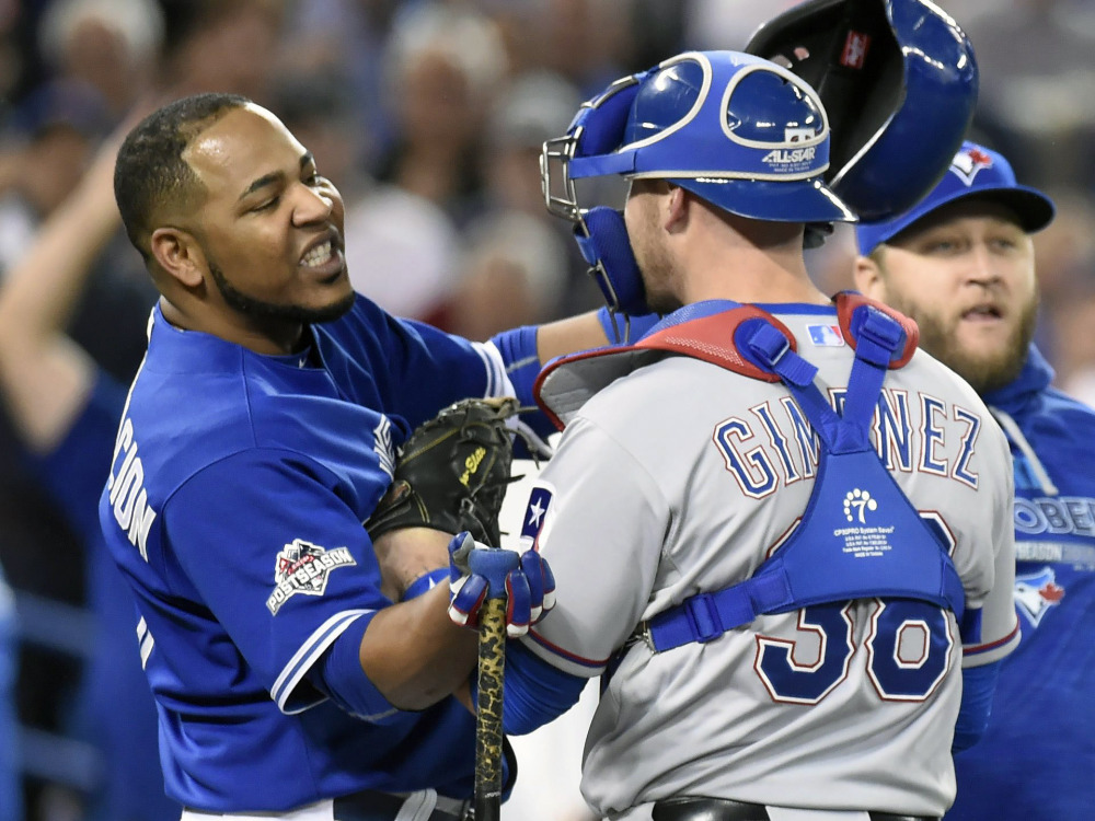 Toronto's Edwin Encarnacion, left, is held by Texas Rangers catcher Chris Gimenez during an altercation as benches clear in the seventh inning. The benches cleared again after Troy Tulowitzki fouled out to end the inning.