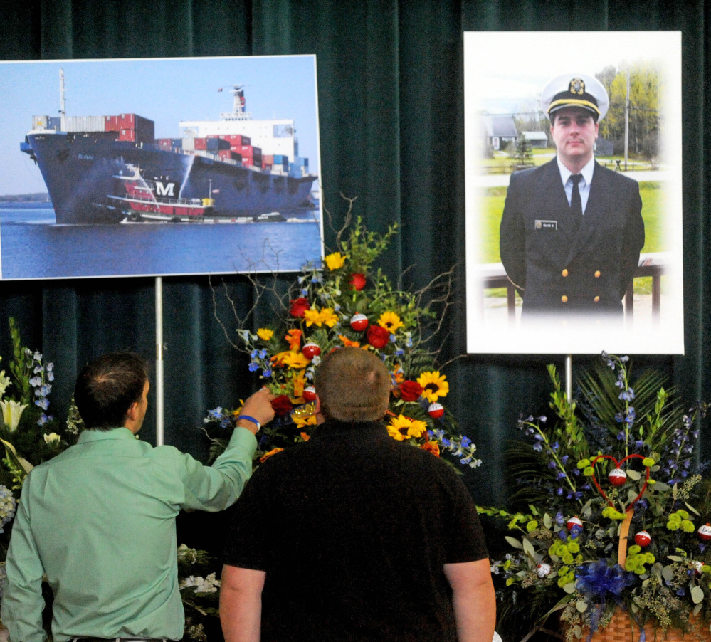 Friends and family pay their respects before a picture of Michael Holland and the cargo ship he worked on during a celebration-of-life ceremony at the Jay Community Building on Wednesday.