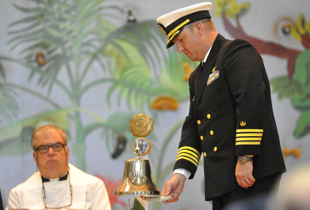 Chaplain Commander Clifford Stuart rings the bell for each life lost on the El Faro during a celebration of crew member Michael Holland's life at the Jay Community Building on Wednesday.
