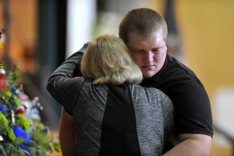 People embrace during a celebration of Michael Holland's life at the Jay Community Building on Wednesday.