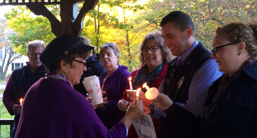 Kathleen Dumont, left, of Kennebec Valley Behavioral Health, lights a candle for Somerset County Sheriff's Office investigator Mike Pike and others at a vigil Wednesday.