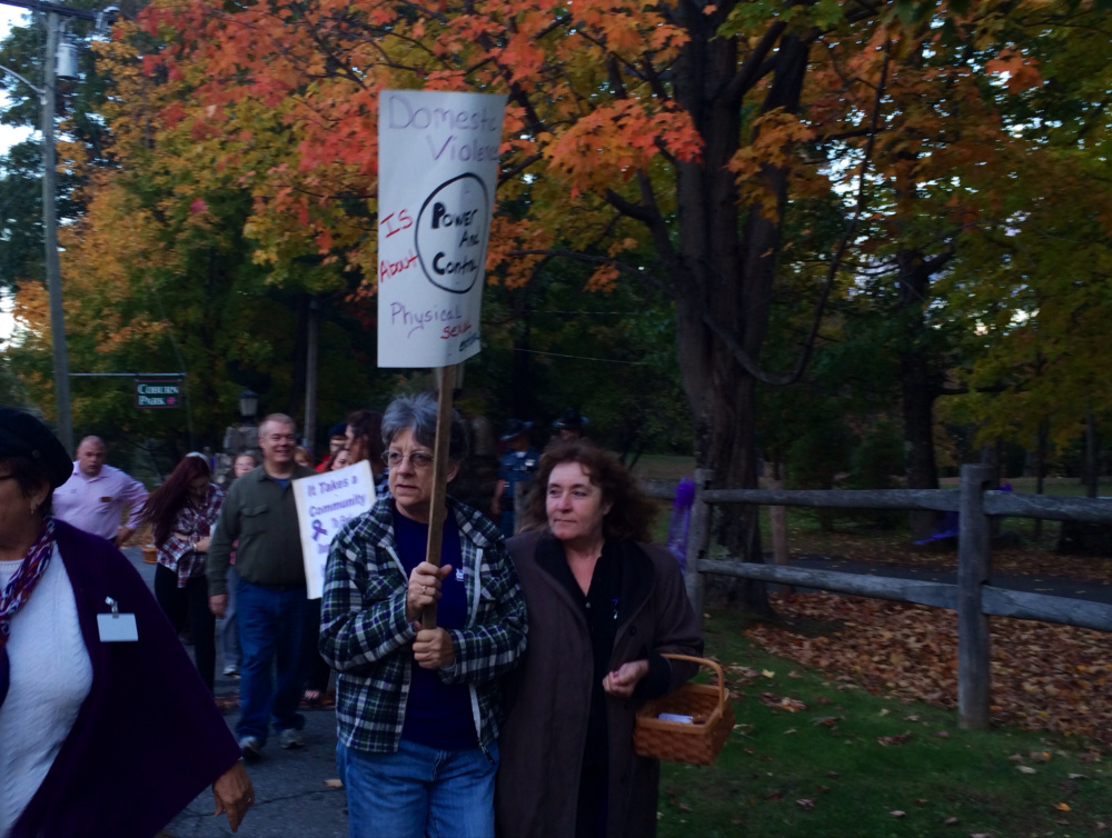 Pat Woodward, left, of Madison, and Pam Morin, right, of Readfield, walk down Water Street in Skowhegan on Wednesday night as part of a domestic violence awareness vigil that started in Coburn Park and proceeded to the Skowhegan Town Office.