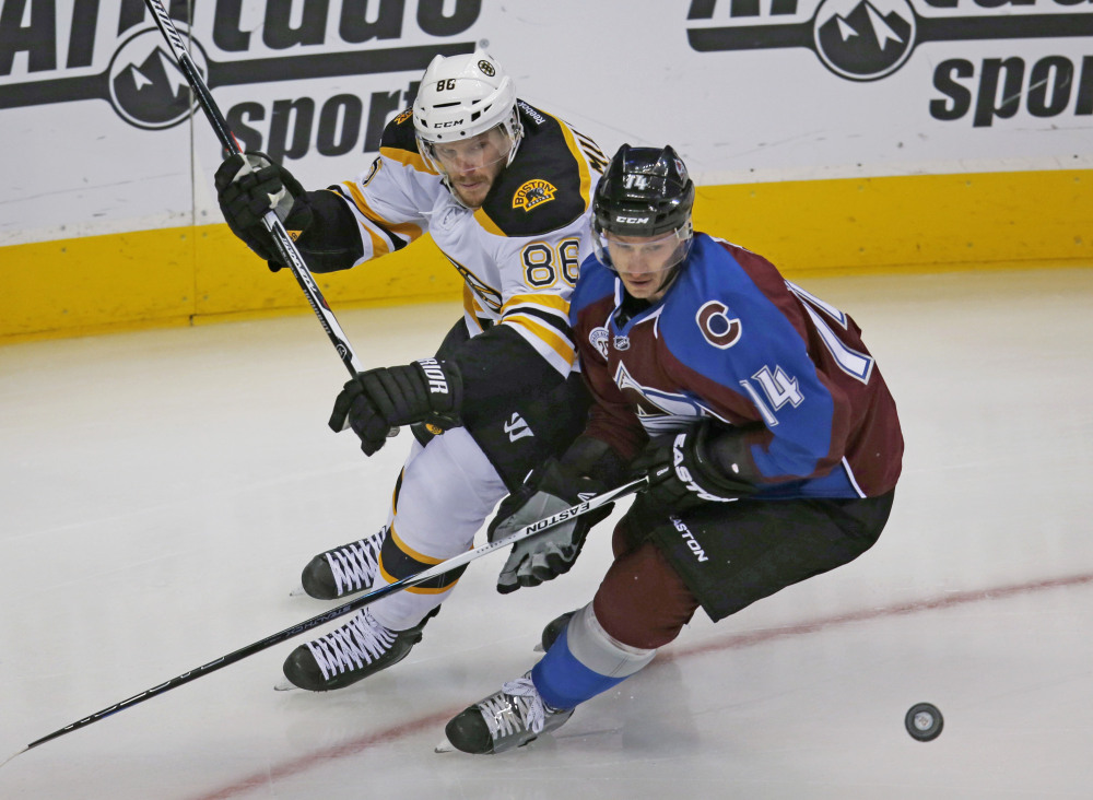 Bruins defenseman Kevan Miller battles with Avalanche left wing Blake Comeau for control of the puck in the first period Wednesday in Denver.