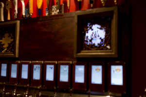 A televised hockey game is reflected in a mirror above the taps on the self-serve beer wall. Gabe Souza/Staff Photographer