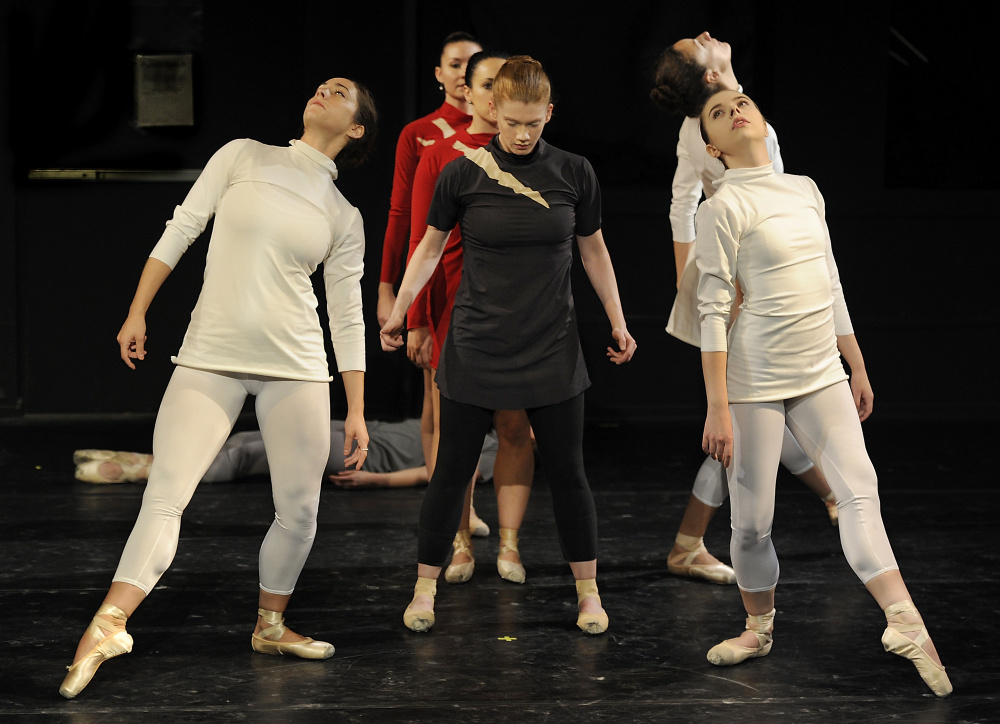 "Portland Ballet dancers rehearse for ""Three Tales by Poe."" ""Investigators,"" in white from left, are Kaleigh Natale, Annie Moore and Erica Diesel; ""Narrator,"" center, is Kaitlyn Hayes; and ""Heartbeats,"" in red, are Amelia Bielen and Deborah Grammatic."