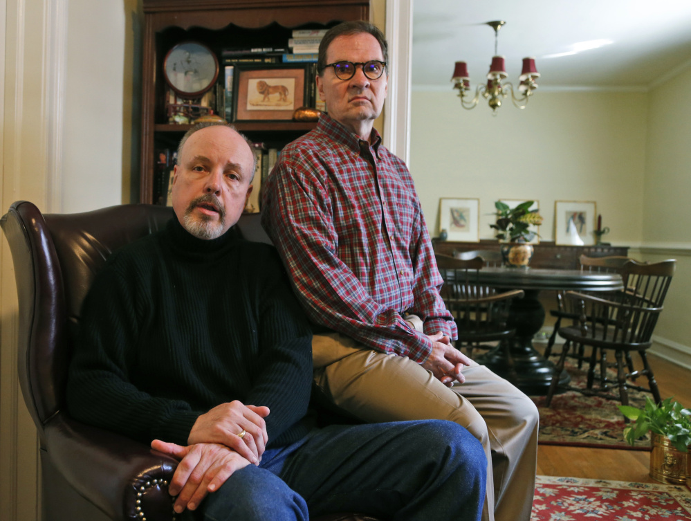 John Murphy, left, who served as executive director of the St. Francis Home, and his husband, Jerry Carter, pose in their home in Richmond, Va.  The Associated Press