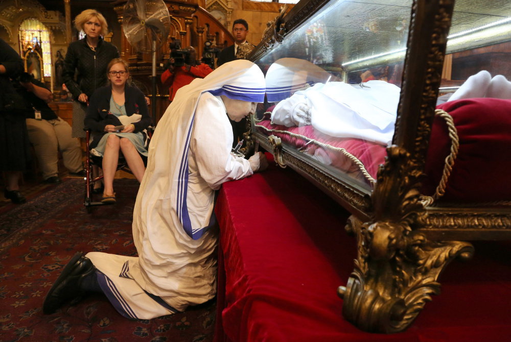 The faithful wait as one prays beside the casket of St. Maria Goretti at St. John Cantius Church in Chicago on Monday. After being stabbed to death while resisting a sexual assault at age 11, the saint is believed to have appeared to her killer.