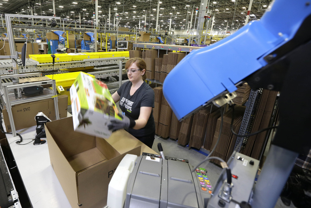 A worker places an item in a box for shipment at the Amazon.com fulfillment center in DuPont, Wash. The center is one of 50 around the country and three in the Puget Sound area that process and ship Amazon customer orders using a mix of robotic technology and human employees.