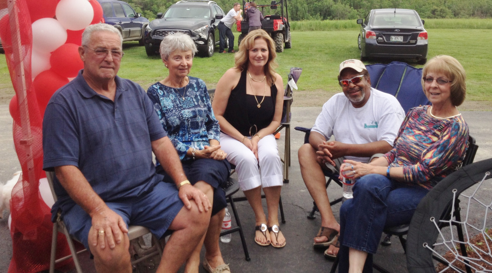 Dan Alexander, left, is shown visiting friends at a graduation party.