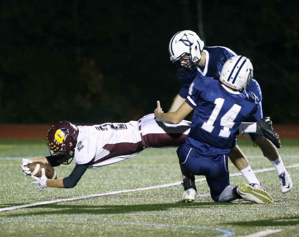 YARMOUTH, ME - OCTOBER 16: Cape Elizabeth at Yarmouth football. Nate Ingalls of Cape Elizabeth reaches to score a touchdown past Noah Eckersley-Ray (#14) and Remi Leblanc of Yarmouth. (Photo by Derek Davis/Staff Photographer)