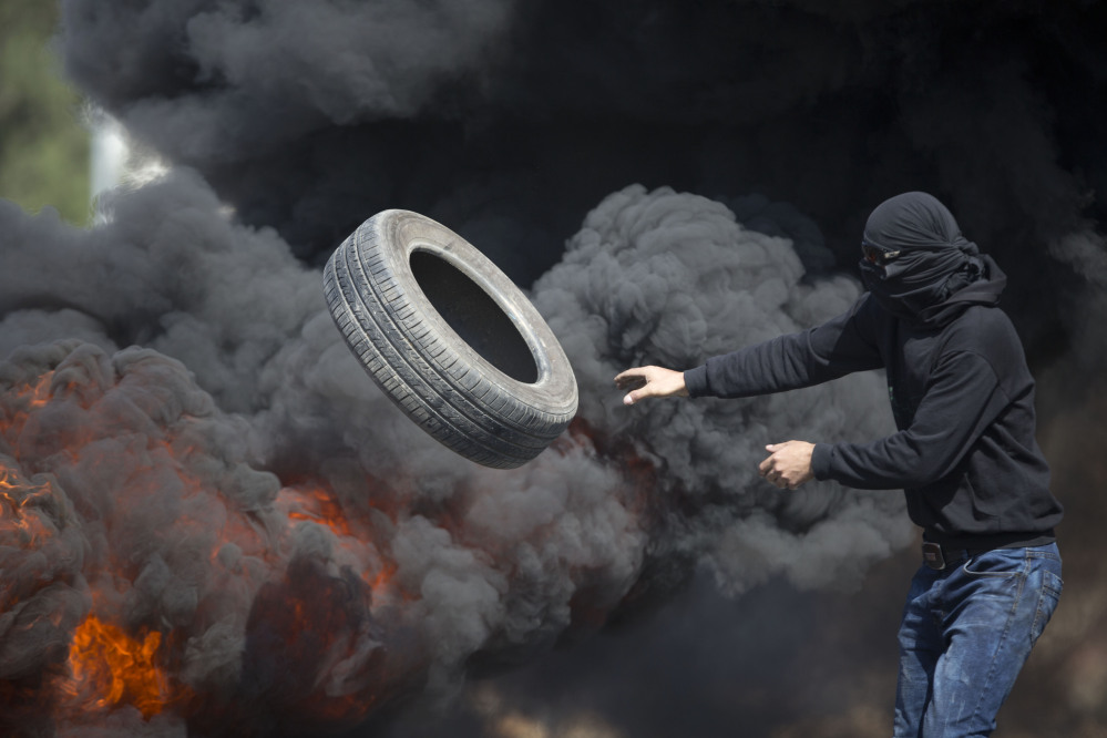 Palestinians burn tires during clashes with Israeli troops near Ramallah, West Bank, Friday. Tensions and violence have been mounting in recent weeks.