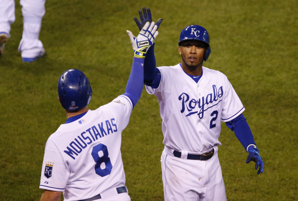 Royals shortstop Alcides Escobar, right, celebrates with third baseman Mike Moustakas after scoring on a double by first baseman Eric Hosmer in the eighth inning in Game 1 of the American League Championship Series against the Toronto Blue Jays on Friday in Kansas City, Mo.