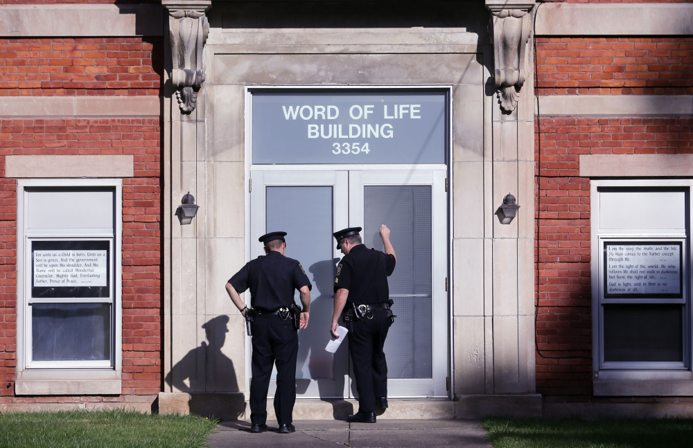 Police knock on the door of the Word of Life Christian Church while serving paperwork on a church member in New Hartford, N.Y. Bruce and Deborah Leonard have been charged in the beating death of their son Lucas and the severe beating of his brother, Christopher.