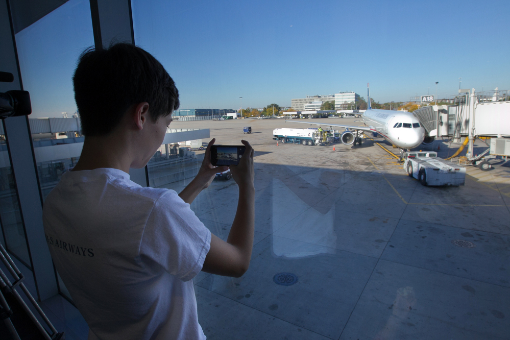 Ethan Hellofs, 13, of Chapel Hill, N.C. photographs the Airbus A-321 he will fly on to Charlotte, N.C., on Friday morning, at Philadelphia International Airport.