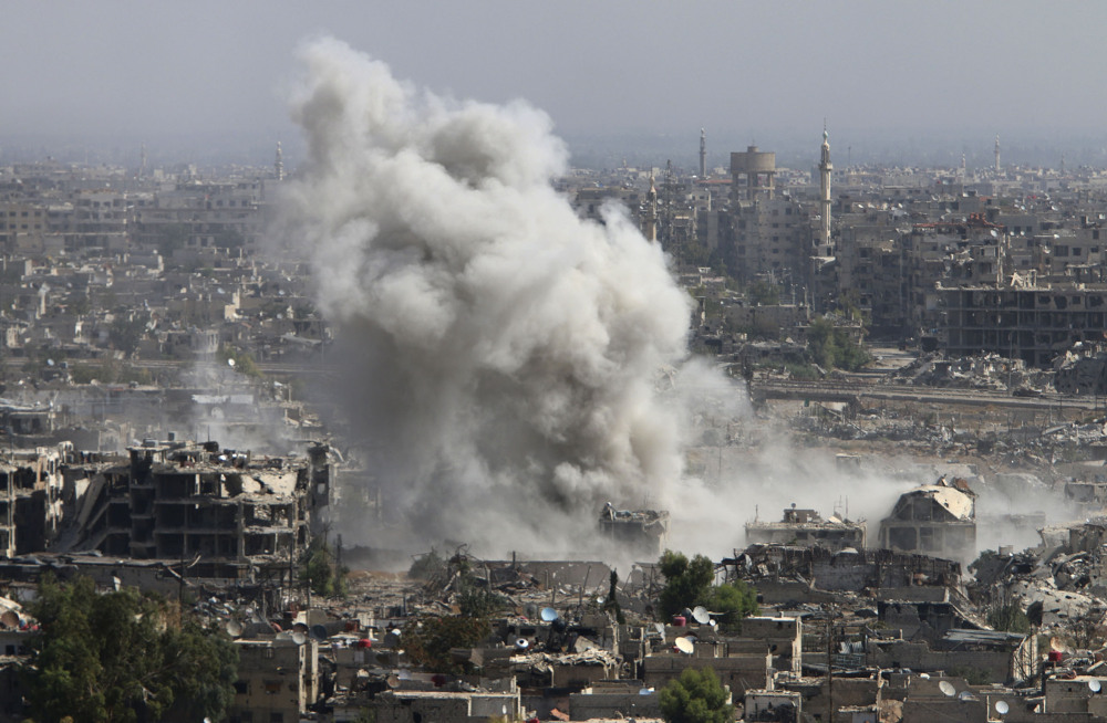 Smoke rises Wednesday after shelling by the Syrian army in Damascus.