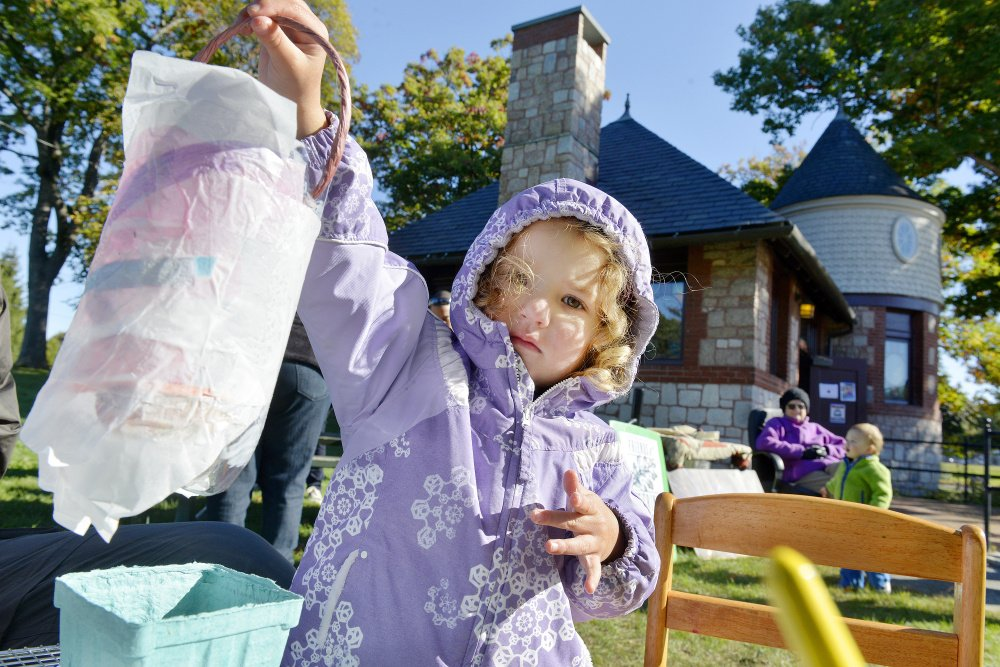 Three-year-old Celia Colson holds up a lantern that she and her father decorated Saturday in a workshop organized by the Friends of Deering Oaks in advance of a Lantern Walk set for Sunday. Celia and her parents, who live in Kansas City, Kan., are visiting Maine.