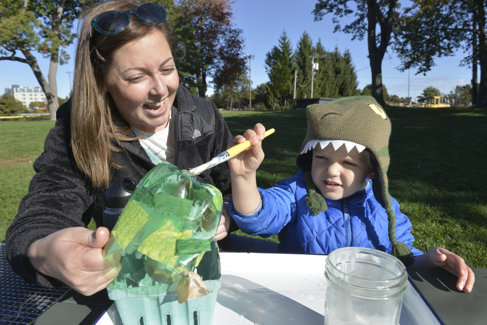 Elaina George of Sidney helps her 4-year-old son, Alexander, as he applies paste to a cut-off plastic bottle before adding colorful strips of paper to make a lantern.