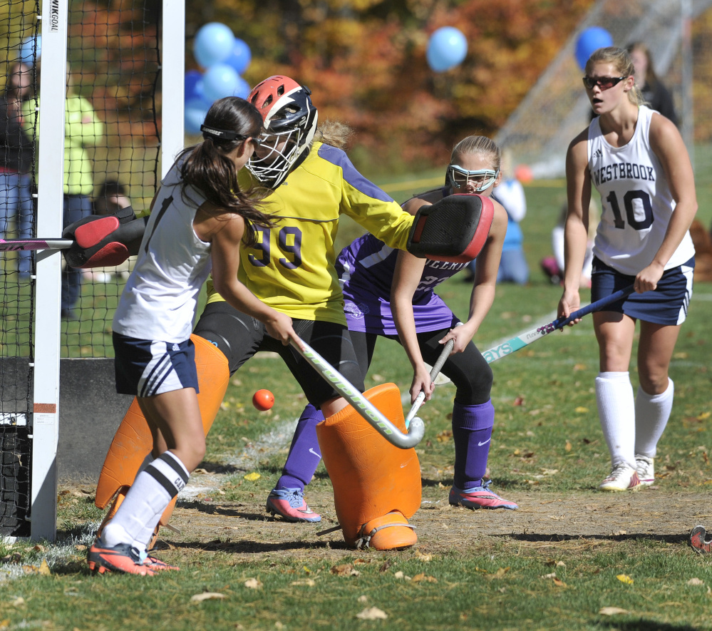 Deering goalie Lillian Frager stops a scoring bid by Westbrook's Abby St. Clair in the second half of a Class A South field hockey prelim Saturday. Westbrook advanced with a 1-0 victory.