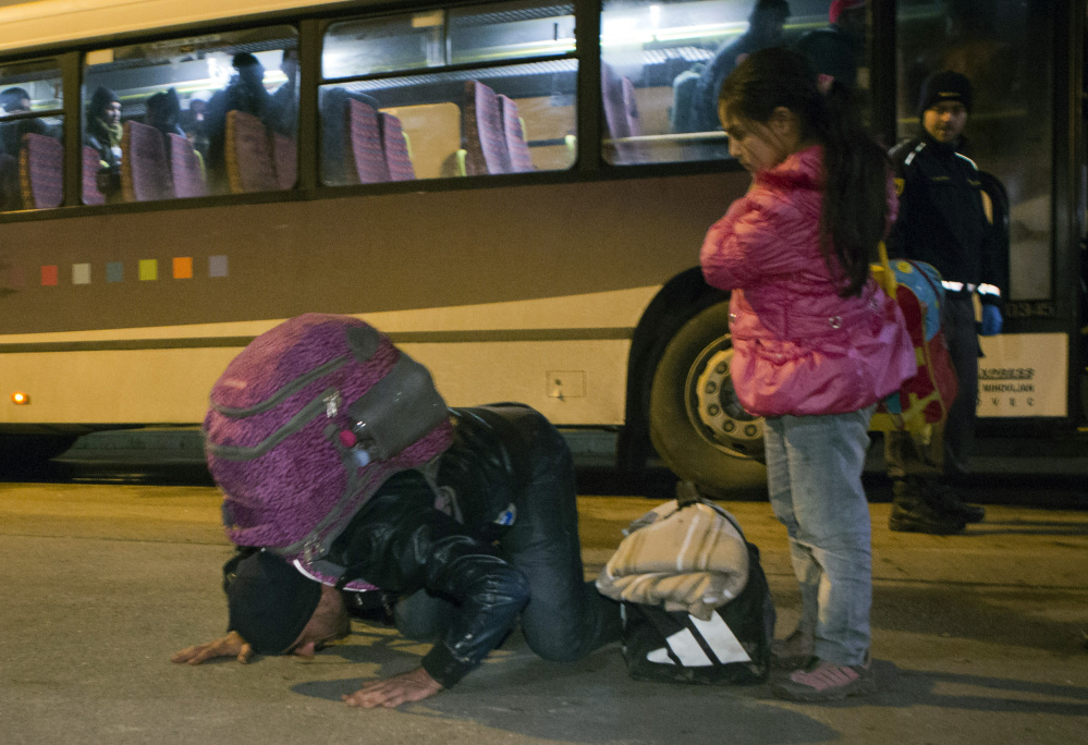 A man kisses the ground after getting off a bus in Lendava, Slovenia, on Saturday. Slovenian officials have said they can permit up to 2,500 migrants per day.