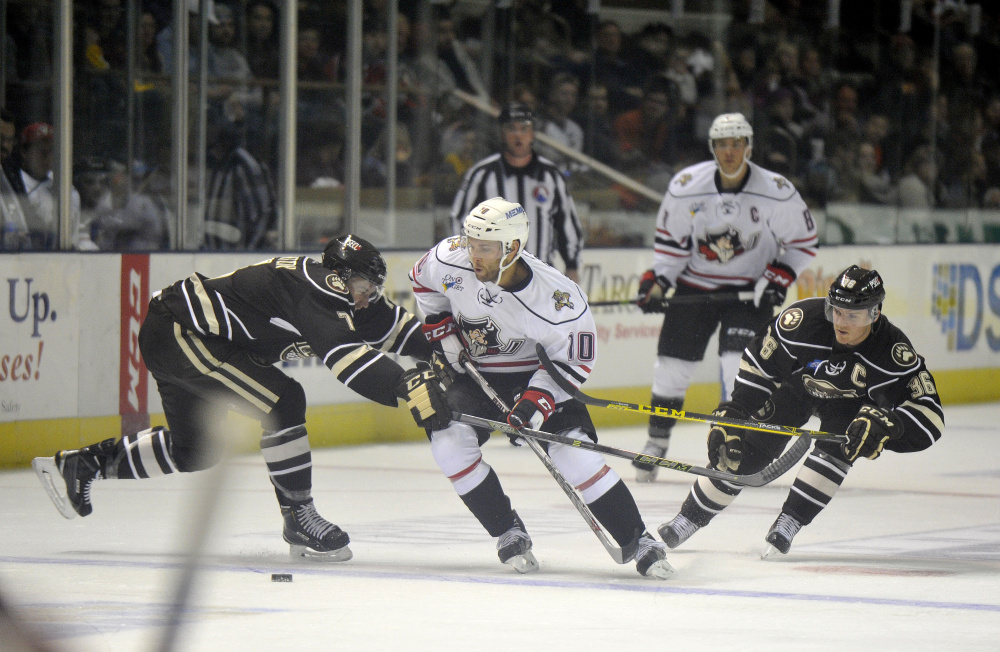 Rob Schremp of the Portland Pirates tries to carry the puck into the Hershey Bears' zone Saturday night while defended by Ryan Stanton, left, and Garrett Mitchell. Portland's first home opener as an affiliate of the Florida Panthers was a 3-2 victory before an announced crowd of 4,275.