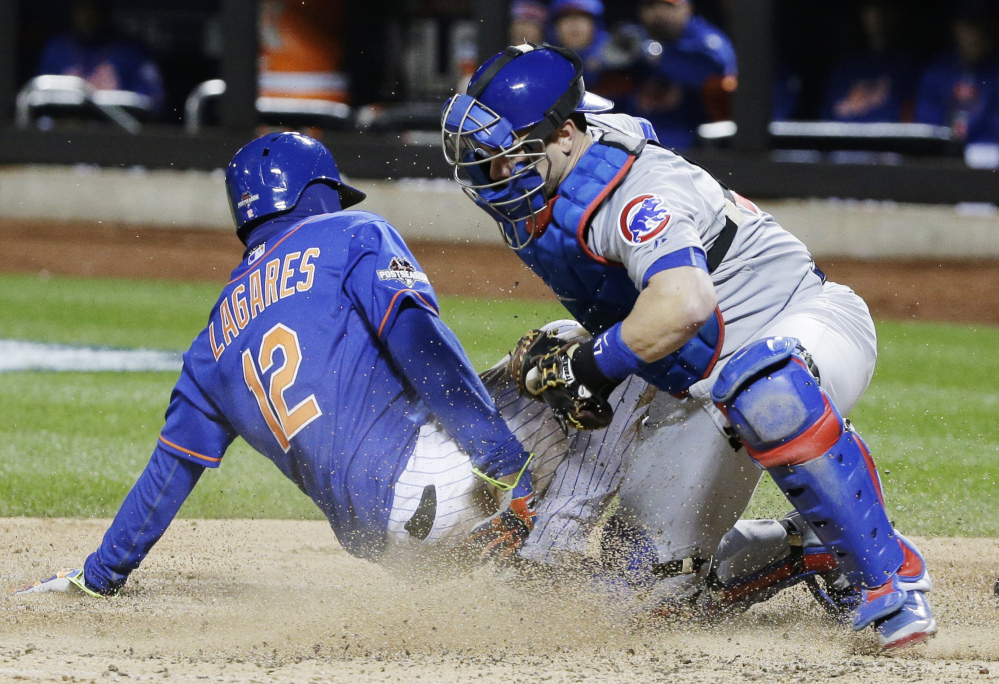 Mets center fielder Juan Lagares slides safely under the tag of Cubs catcher Miguel Montero in the seventh inning of Game 1 of the National League baseball championship series Saturday in New York. Lagares scored from third on a sacrifice fly by Curtis Granderson.