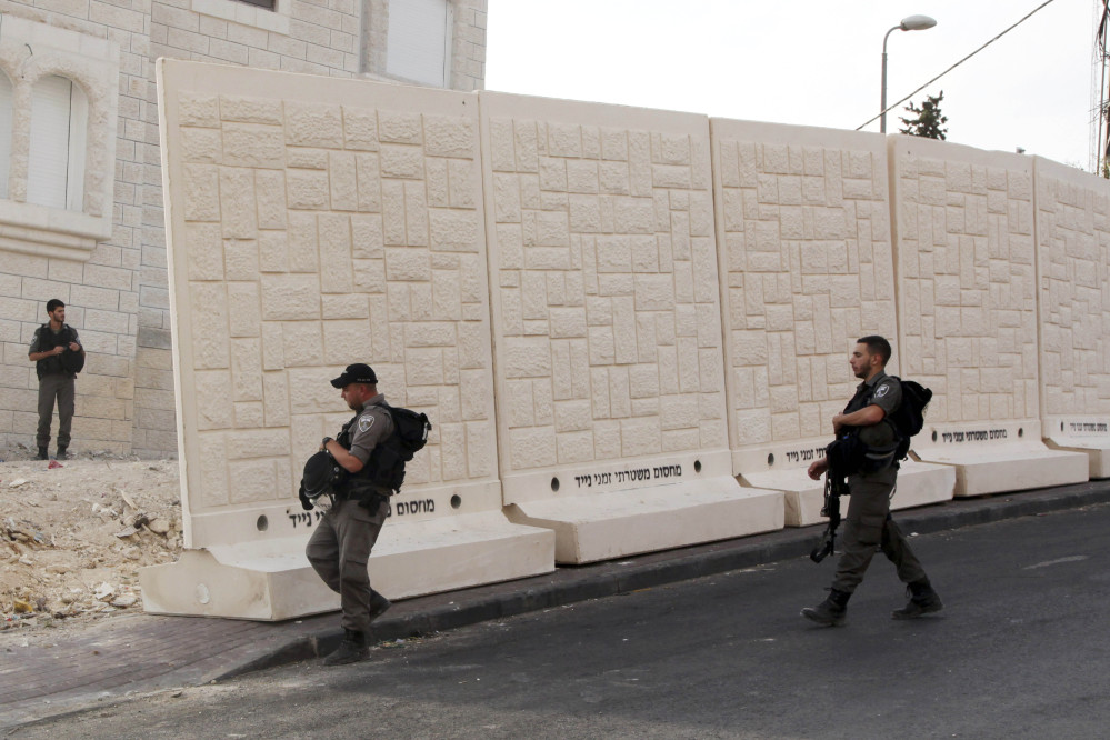 Israeli border police walk by a wall being built between Palestinian and Jewish neighborhoods in Jerusalem.