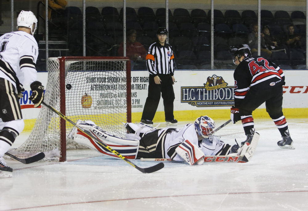 Kyle Rau flips the puck over Hershey Bears goalie Dan Ellis for a second-period goal. Rau scored twice to help the Pirates complete a weekend sweep of Hershey.