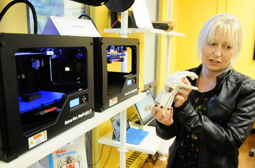 Staffer Becky LaBonte talks about a hand she built from parts made on a 3-D printer during an event on Thursday at the Maine State Library in Augusta.