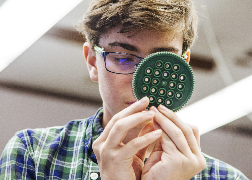 Freshman Hal Clews examines a gear to count its teeth during a small-group portion of his early college engineering class at Portland High School.