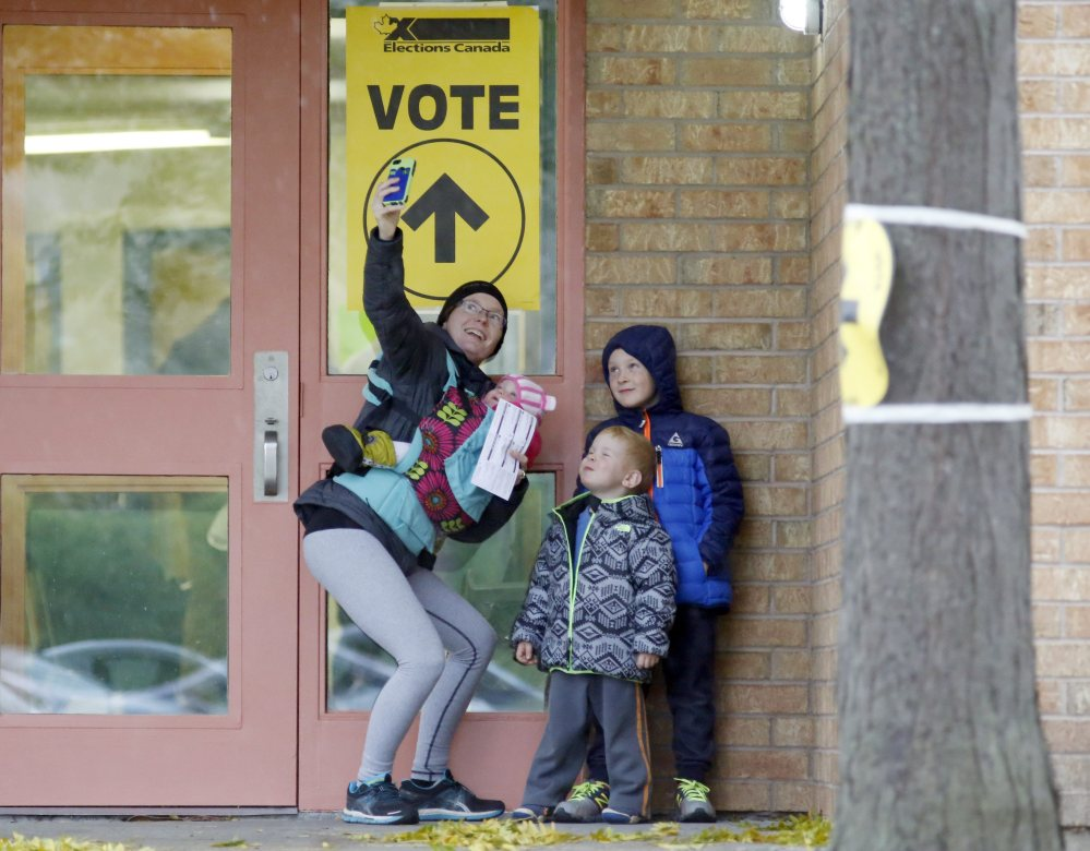 Alexandra Pettit takes a selfie with her kids at the Gloucester Presbyterian Church polling station in Ottawa, after casting her vote in the Canadian federal election on Monday.