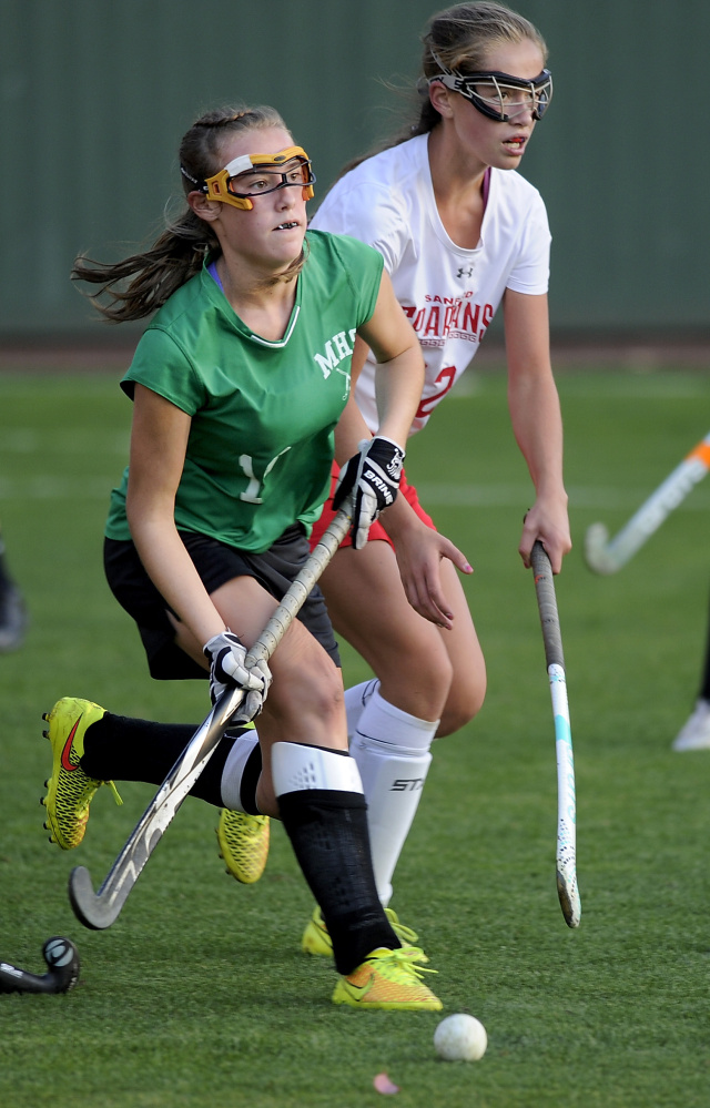 Emma Desrochers of Massabesic takes the ball down the field and looks for a teammate Tuesday while being shadowed by Bridget Duckworth of Sanford during Sanford's 1-0 victory in the Class A South field hockey quarterfinals.