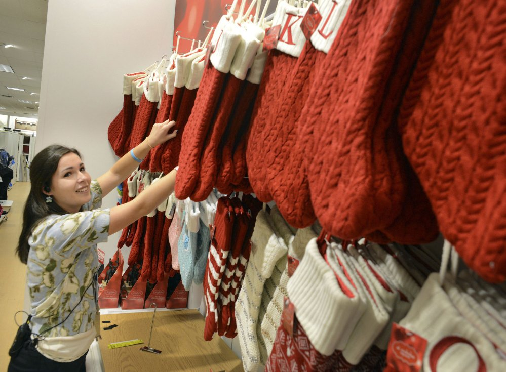 Megan Shoemaker of Fairless Hills, Pa., works on a Christmas stocking display at Kohl's in Yardley, Pa. Kohl's plans to add 69,000 seasonal jobs, with hiring to start this month.