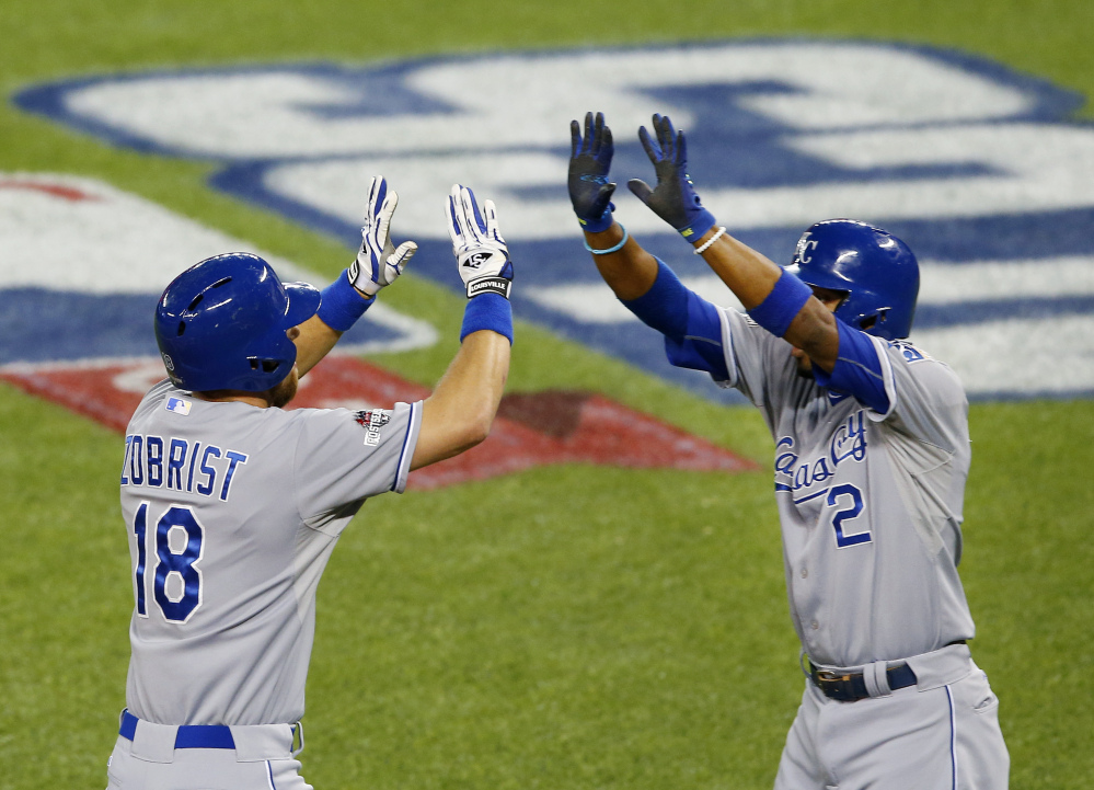 The Royals' Ben Zobrist, left, celebrates his two-run home run with Alcides Escobar in the first inning of Tuesday's American League Championship Series game in Toronto.