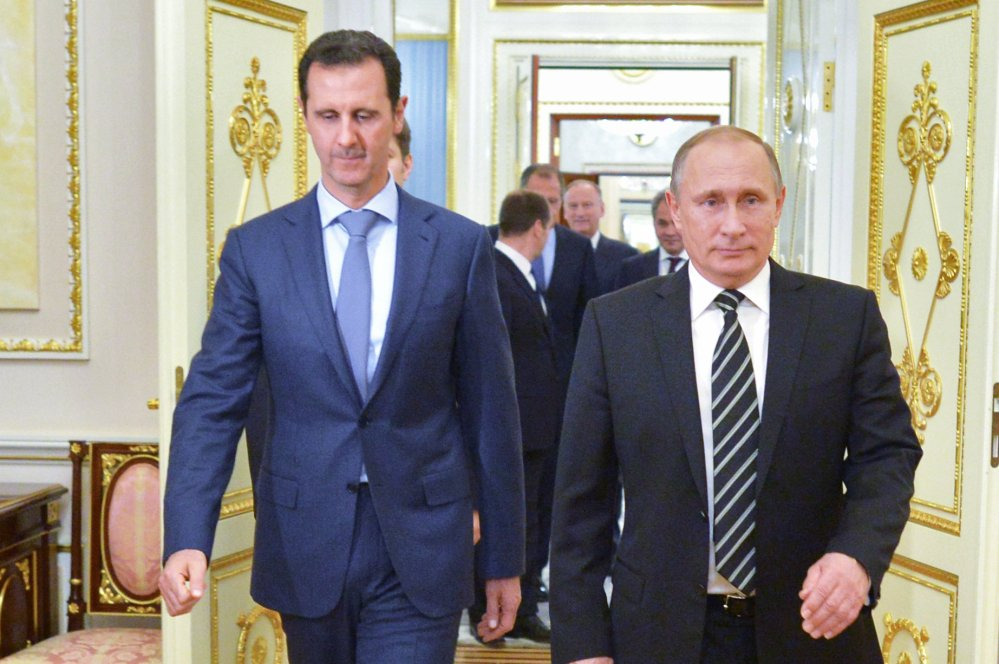 Russian President Vladimir Putin, right, and Syrian President Bashar Assad arrive for a meeting Wednesday.