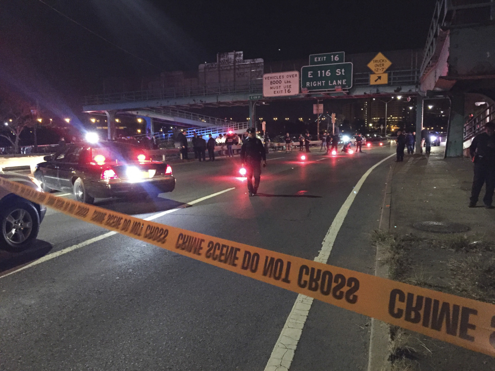 Police officers investigate along FDR Drive at East 120 Street on Tuesday in New York where a New York City police officer was fatally shot.