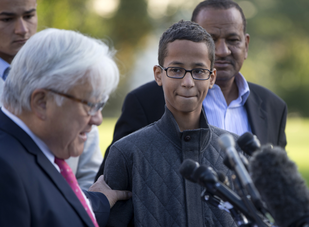Ahmed Mohamed, second from right, listens as Rep. Mike Honda, D-Calif., left, speaks during a news conference on Capitol Hill in Washington on Tuesday. The Associated Press