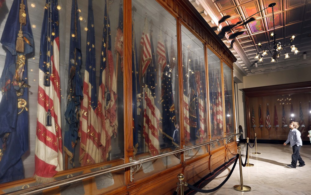 "A fourth-grader visits the Hall of Flags in New Hampshire's Statehouse in Concord. The flags, many of them dating from the Civil War, are deteriorating because their glass cases are not air-tight. The display has made the New Hampshire Preservation Alliance's ""Seven to Save"" list this year."